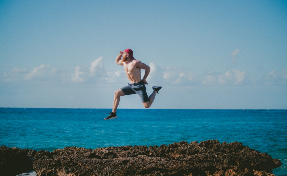 Man jumping on rocks by the ocean